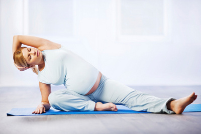 Young pregnant woman doing stretching exercise.