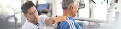 Frau liegt auf dem Trainingsbank und hält Hantel in den Händen, Physiotherapeut stützt sie von hinten