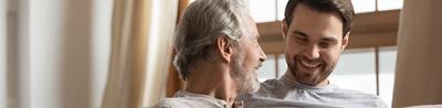Älterer und jüngerer Mann auf Sofa