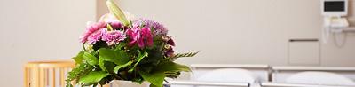 Blumenstrauss vor einem Spitalbett und einem Kinderbettchen
