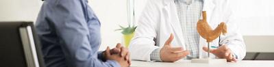 Patientin und Arzt in Sprechstunde mit Magenmodell
