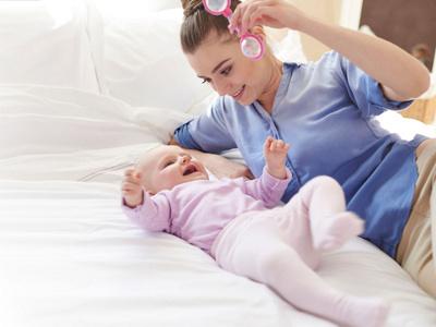 Mutter spielt mit Baby auf Bett