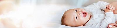 Lachendes Baby auf Bett liegend