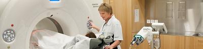 Pflegefachperson und Patientin am CT