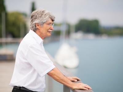 Patient hält sich an Geländer und schaut auf den See