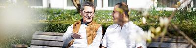 Patient sitzt mit Pfleger auf einer Bank