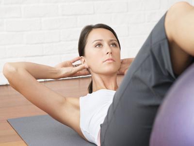 Frau macht Übungen auf dem Boden