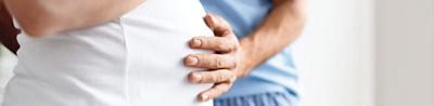 Mann platziert Hand auf Bauch der Frau