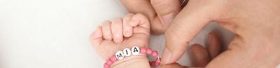 Baby mit einem Namenskettchen um den Arm