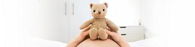 Teddy auf Bauch von einer schwangeren Frau