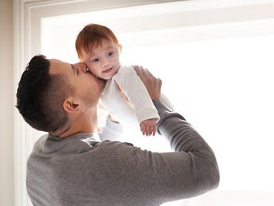Vater gibt seinem Kind einen Kuss auf die Wange