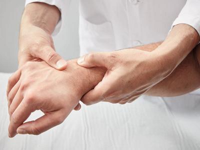 Arzt tastet Hand des Patienten ab