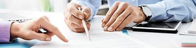 Nahaufnahme von Händen mit Bleistift, die auf ein Blatt Papier zeigen