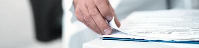 Nahaufnahme einer Hand die durch ein Stappel Dokumente blättert