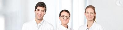 Zwei Ärzte und eine Pflegefachperson stehen nebeneinander und schauen in die Kamera