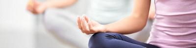 Ausschnitt vom Oberkörper einer Frau, die Yoga praktiziert und die Hand auf dem Knie aufgelegt hat