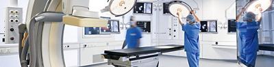 Aufnahme des Hybridoperationssaals, im Zentrum eine Liege und zwei Operationsfachangestellte