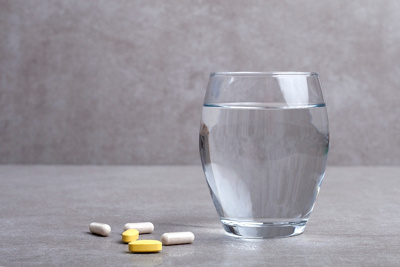 glass of water and pills on gray background