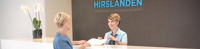 Empfangsmitarbeiterin und Patientin beim Klinikeintritt