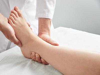 Arzt untersucht Fuss eines Patienten