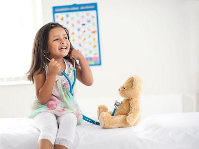Kind hört Teddybär mit Stethoskop ab
