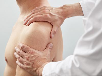 Arzt untersucht Schulter eines Patienten
