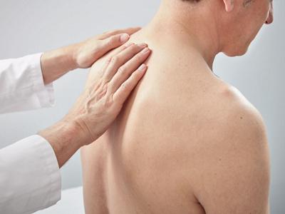 Arzt untersucht Rücken und Wirbelsäule eines Patienten